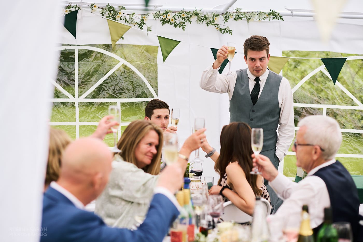 Best main raises glass to toast during wedding speeches in small garden marquee