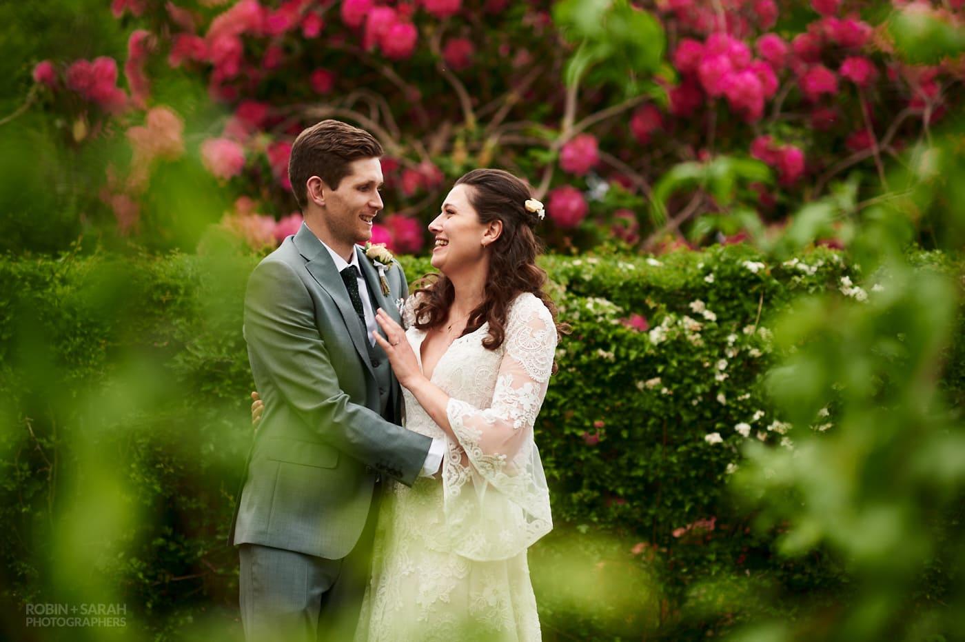 Bride and groom relaxing in garden during evening