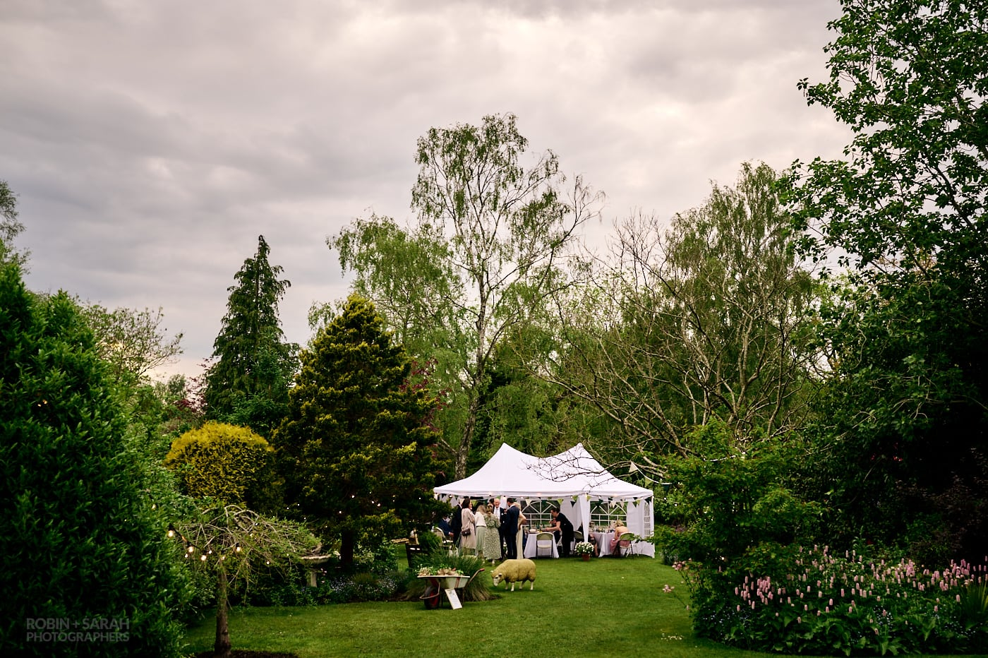 Marquee in garden with wedding guests enjoying the evening