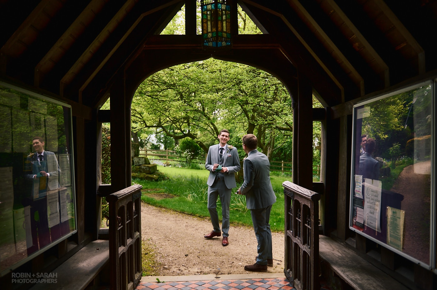 Groom and best man chat outside church before wedding service