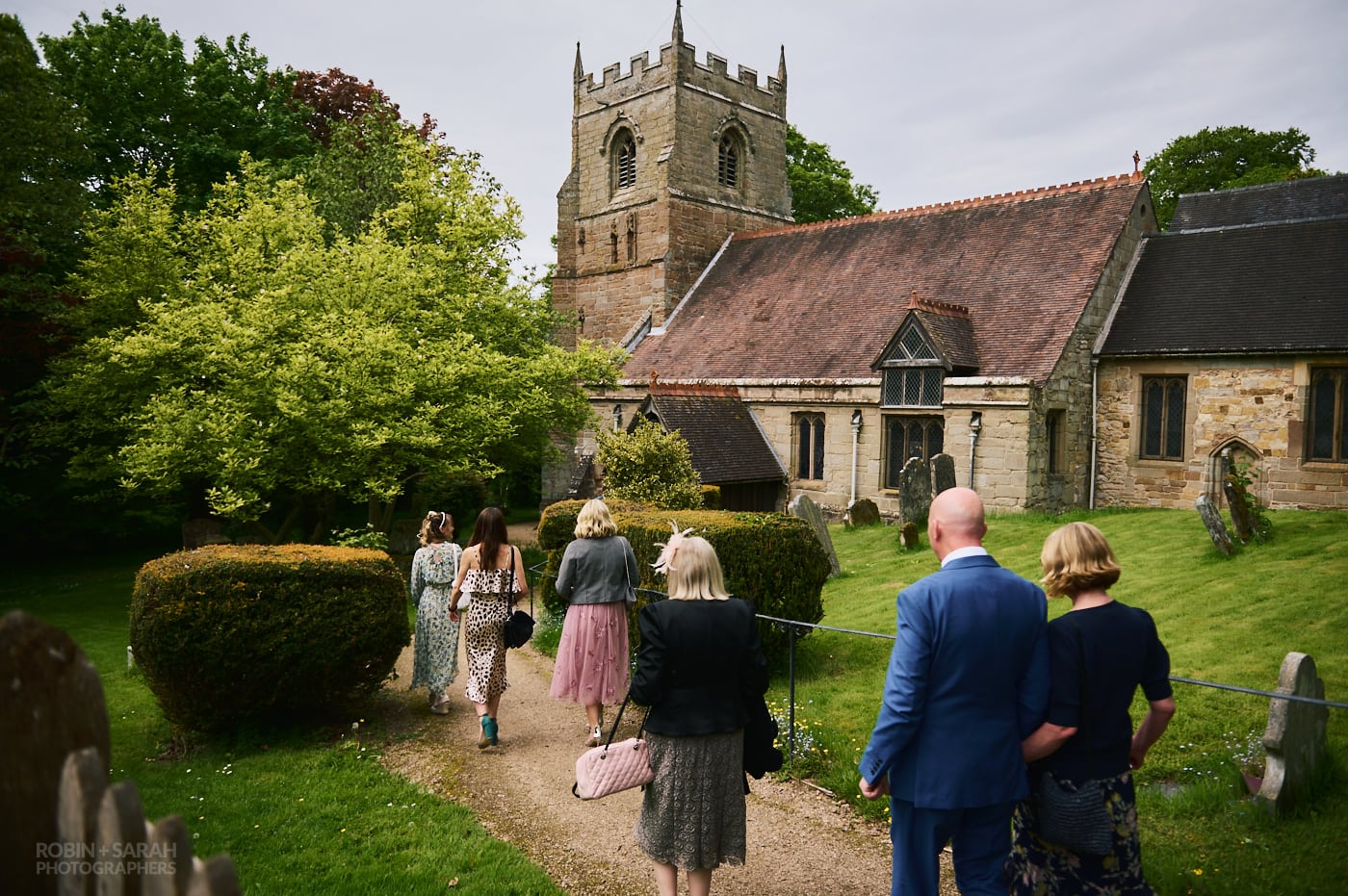 Wedding guests arrive at Beoley church for wedding