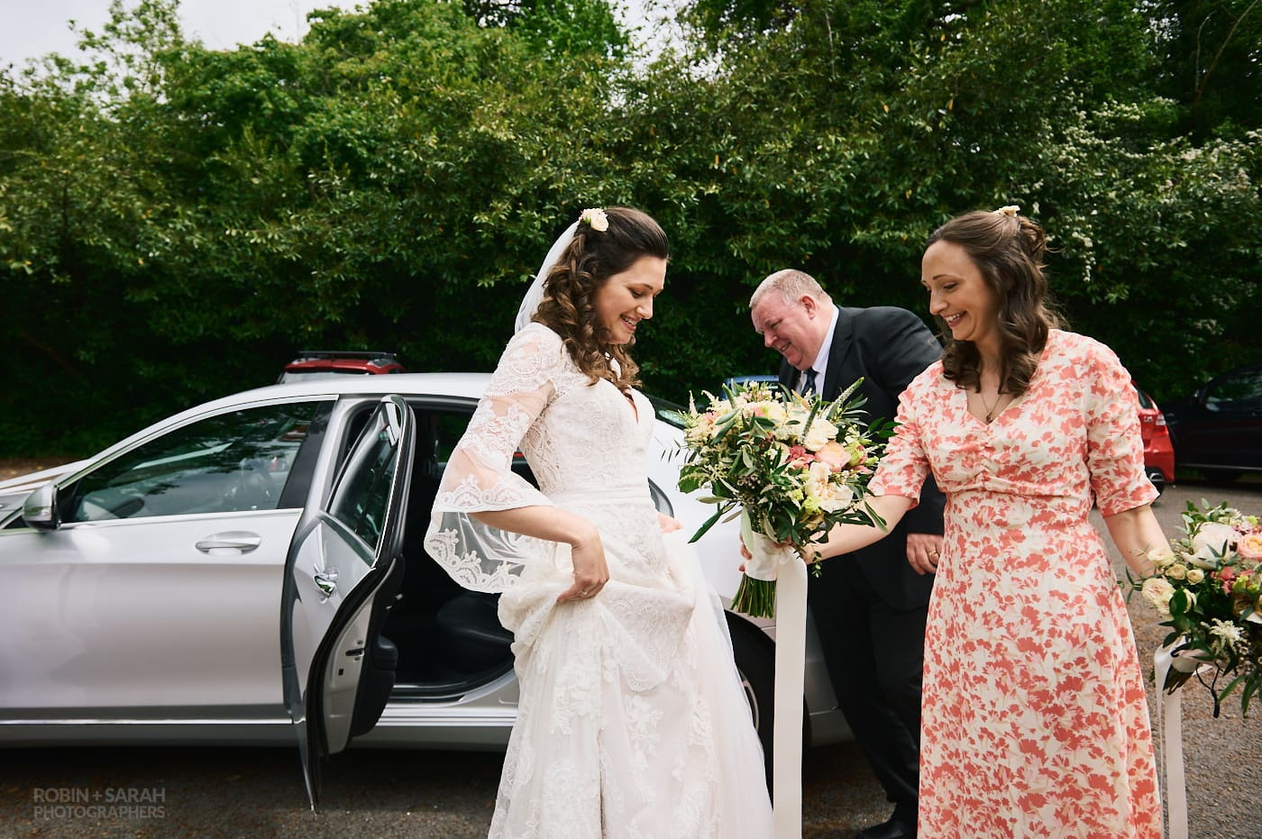 Bride and bridesmaid get out of wedding car