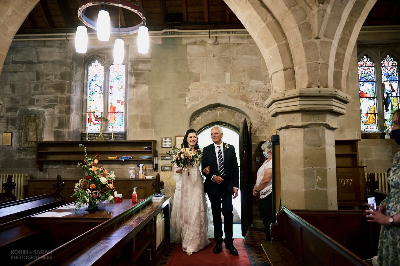 Bride and dad enter St Leonrd's church Beoley for wedding service
