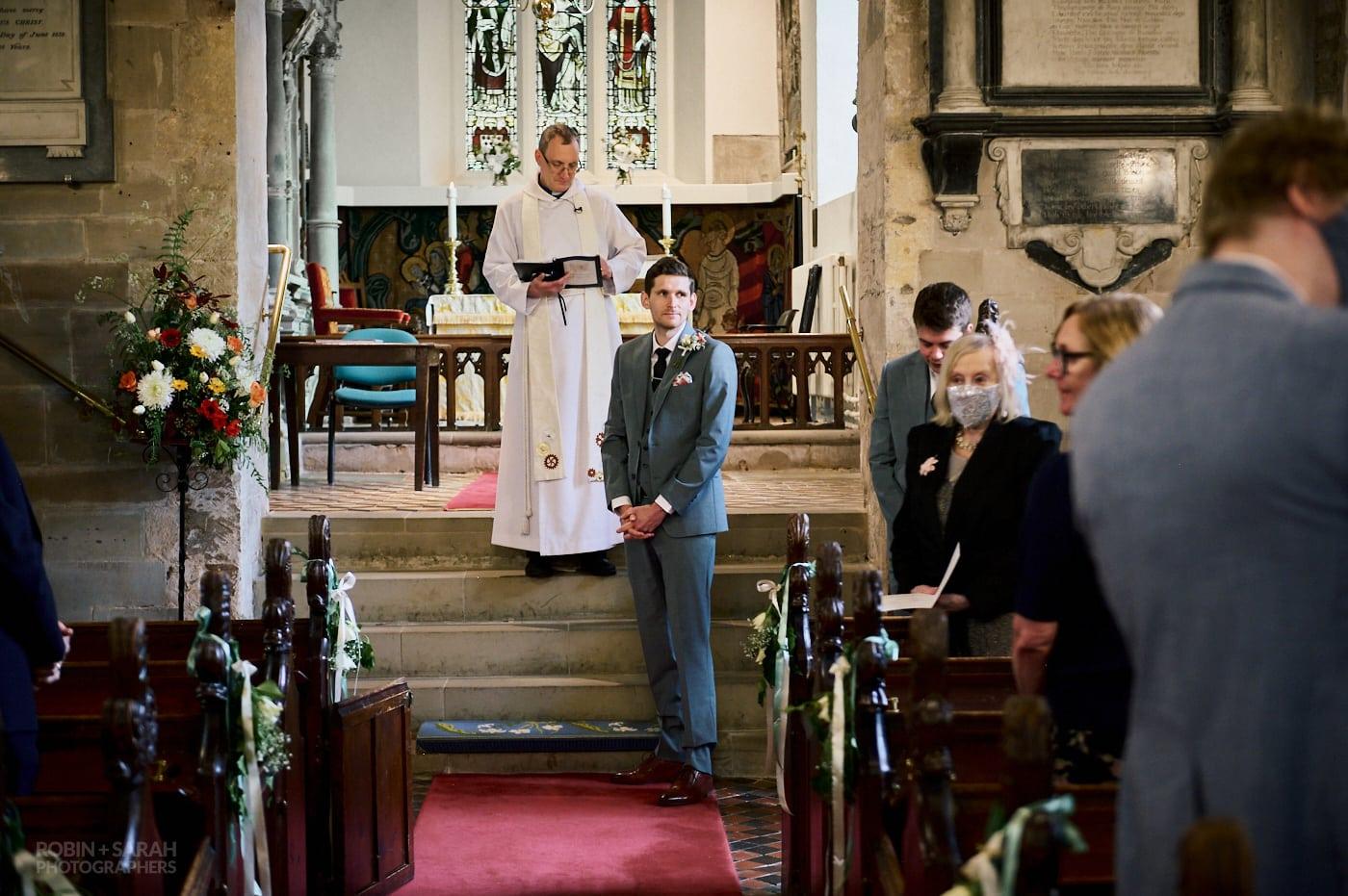 Groom waits for bride at church wedding