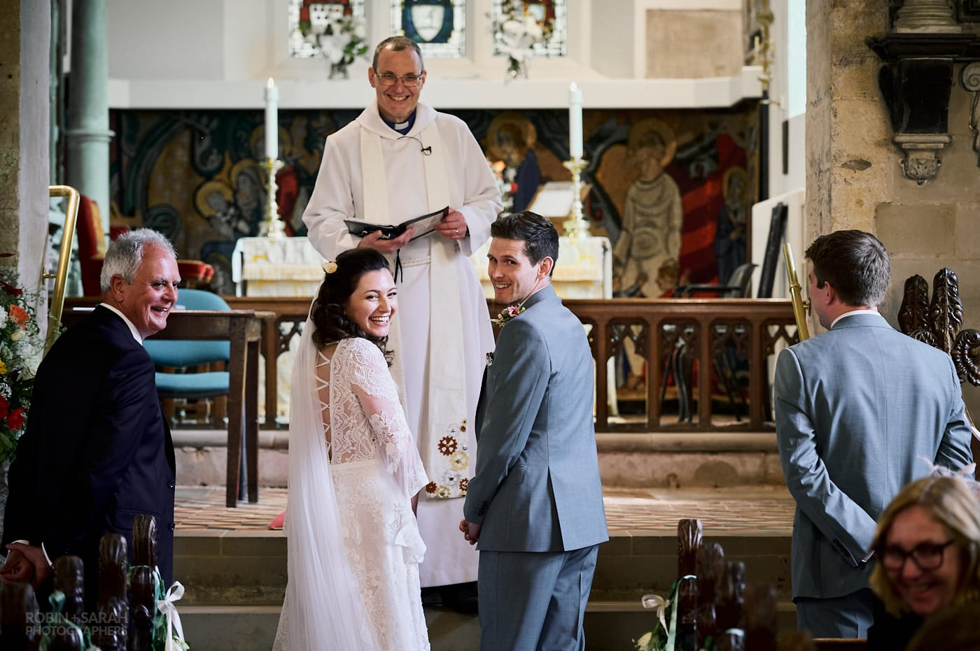 Bride and groom turn to look at guests during wedding ceremony