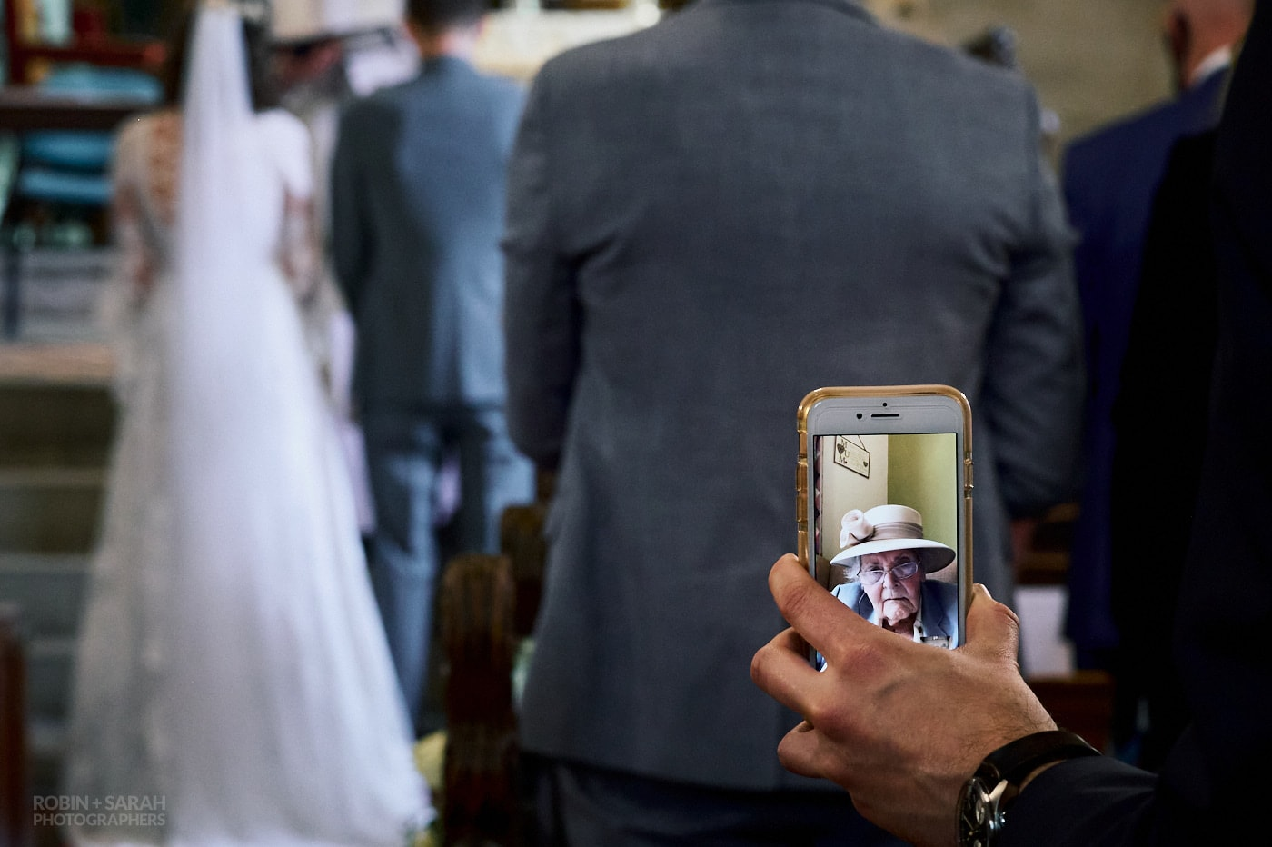 Wedding guests holds mobile phone videoing wedding ceremony as grandmother watches on live feed