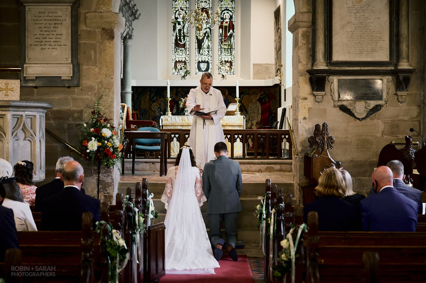 Bride and groom take blessing from vicar during church wedding service