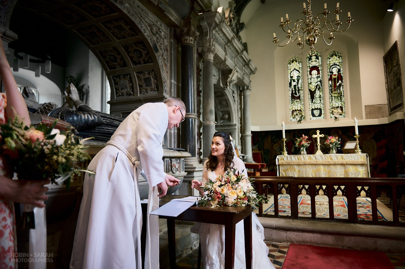 Bride signs marriage register at St Leonard's church Beoley
