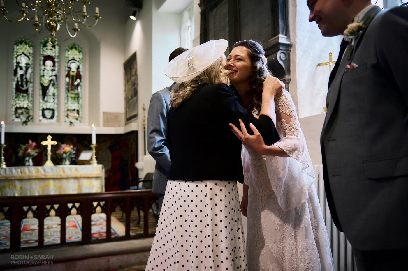 Bride hugs mum at St Leonard's church wedding