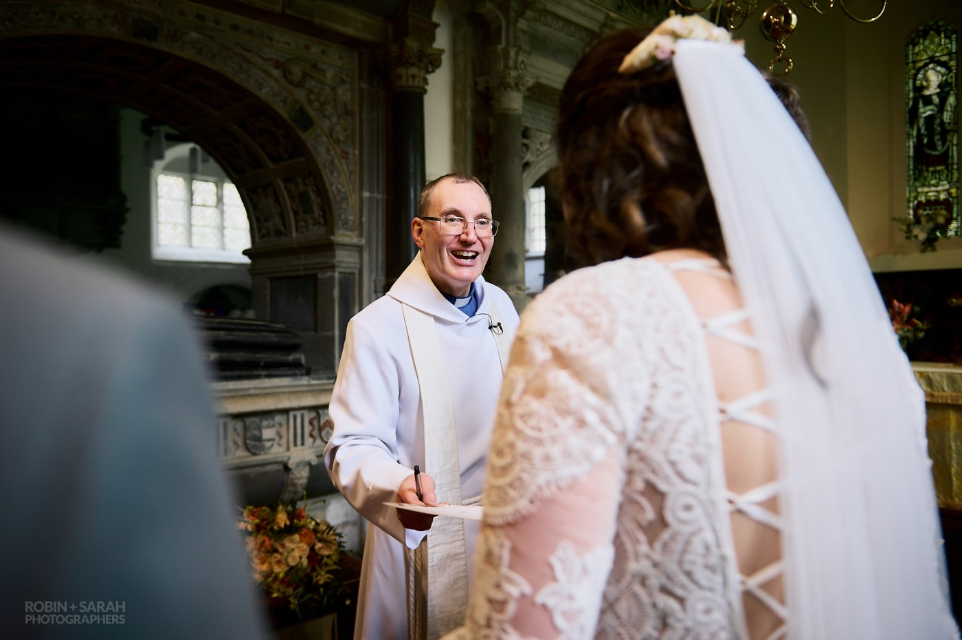 Vicar gives bride wedding certificate at Beoley church