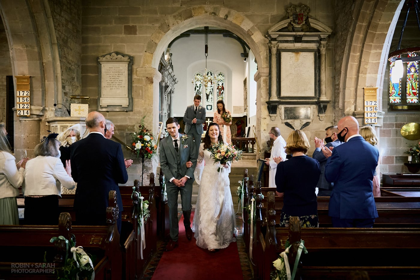 Bride and groom down aisle after wedding ceremony at St Leonard's Beoley
