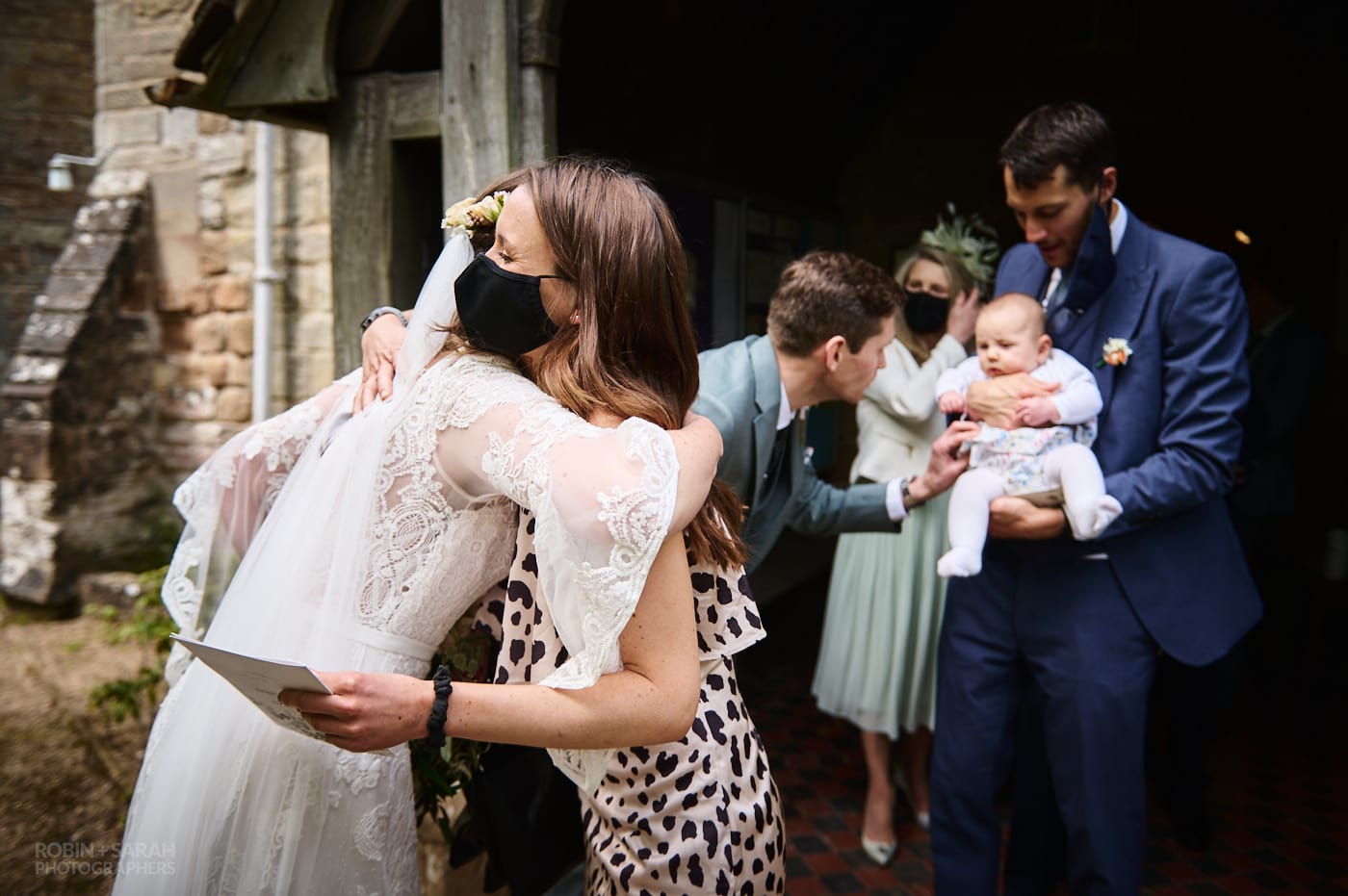 Bride hugs wedding guest after church ceremony