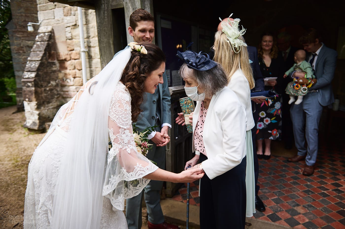 Bride hugs grandmother after wedding at Beoley church