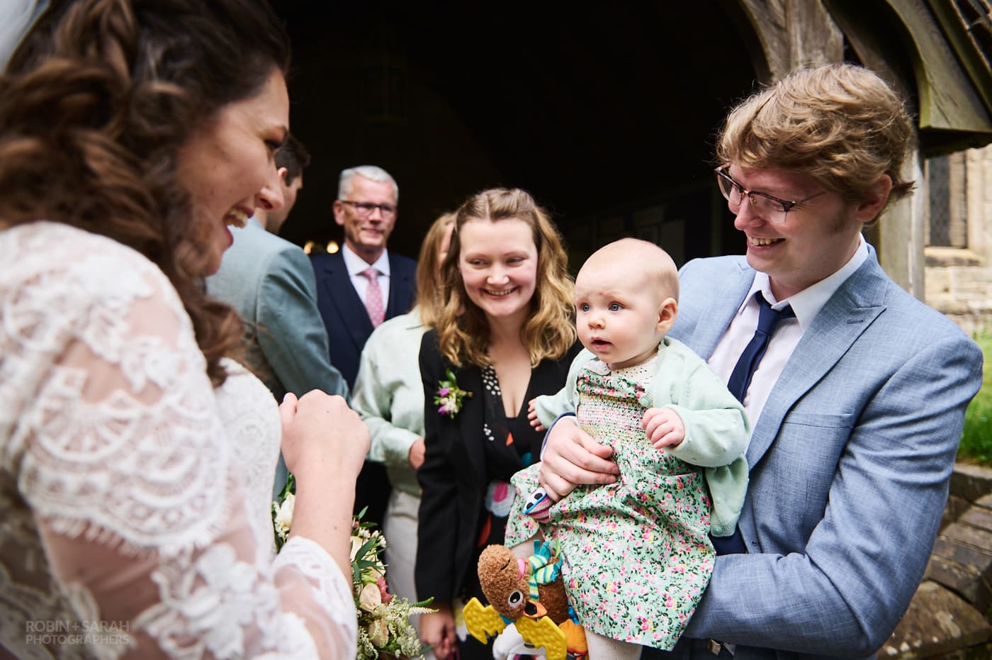 Bride greets wedding guests after church ceremony