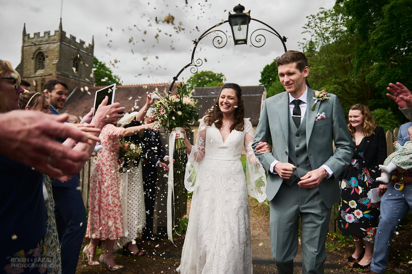 Newly married bride and groom walk as wedding guests throw confetti at St Leonard's church Beoley