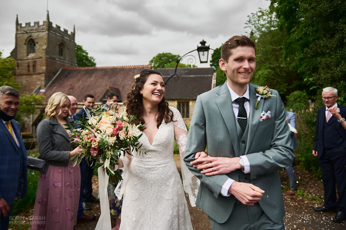 Newly married bride and groom walk as wedding guests throw confetti