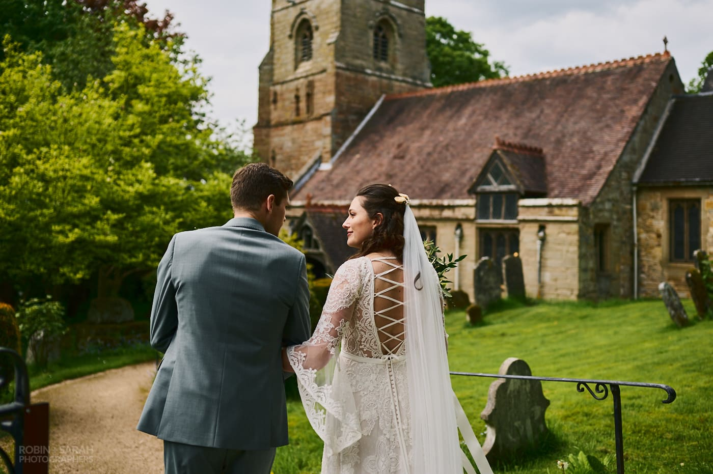 Bride and groom walking together at St Leonard's church Beoley