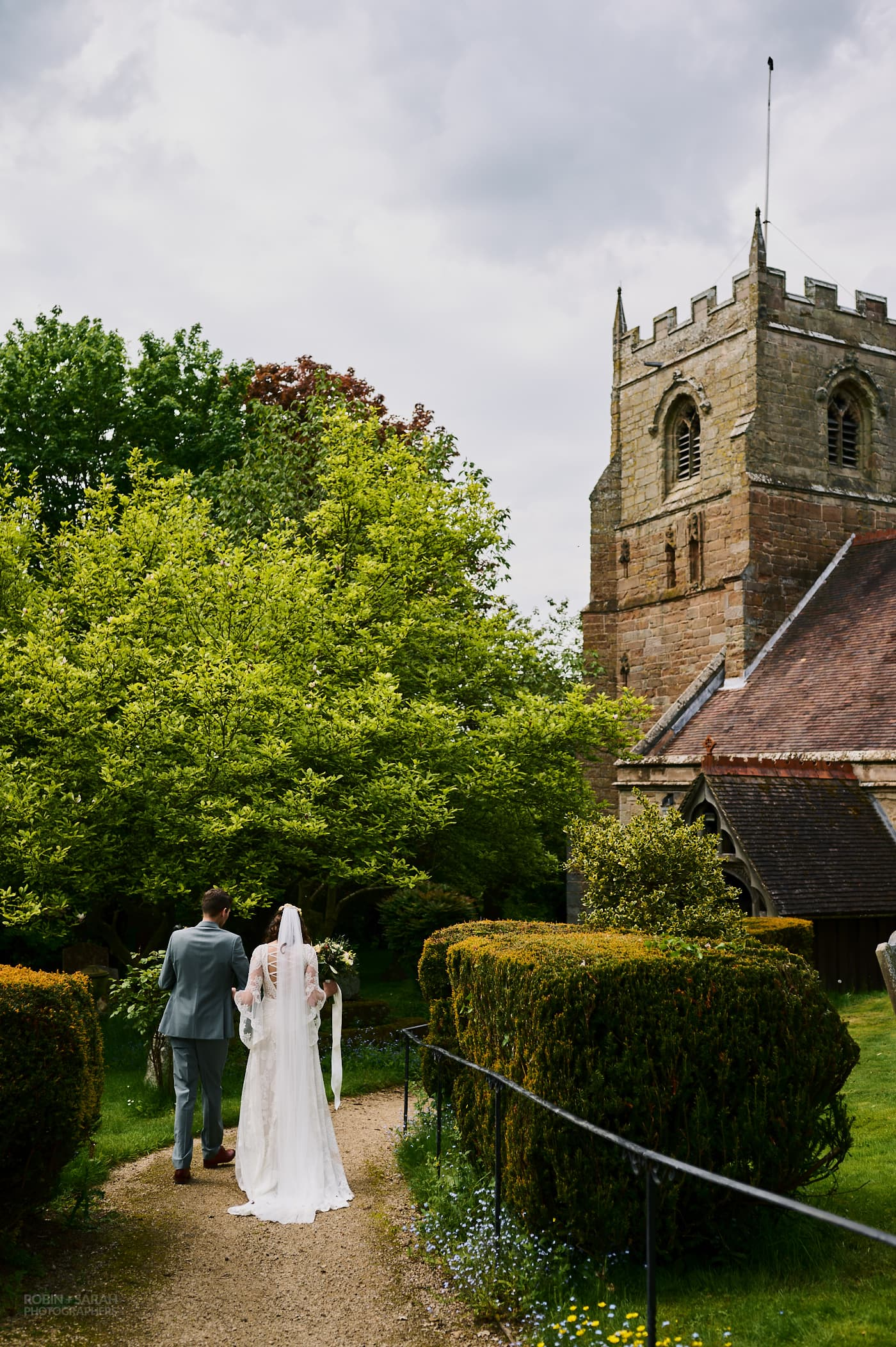 Bride and groom walk down path together at Beoley Church