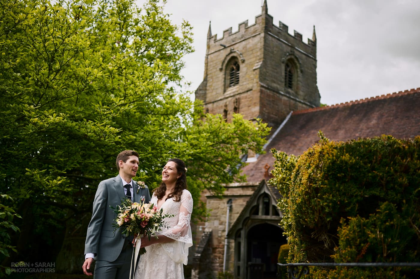 Bride and groom relax together in front of St Leonard's church in Beoley, Redditch