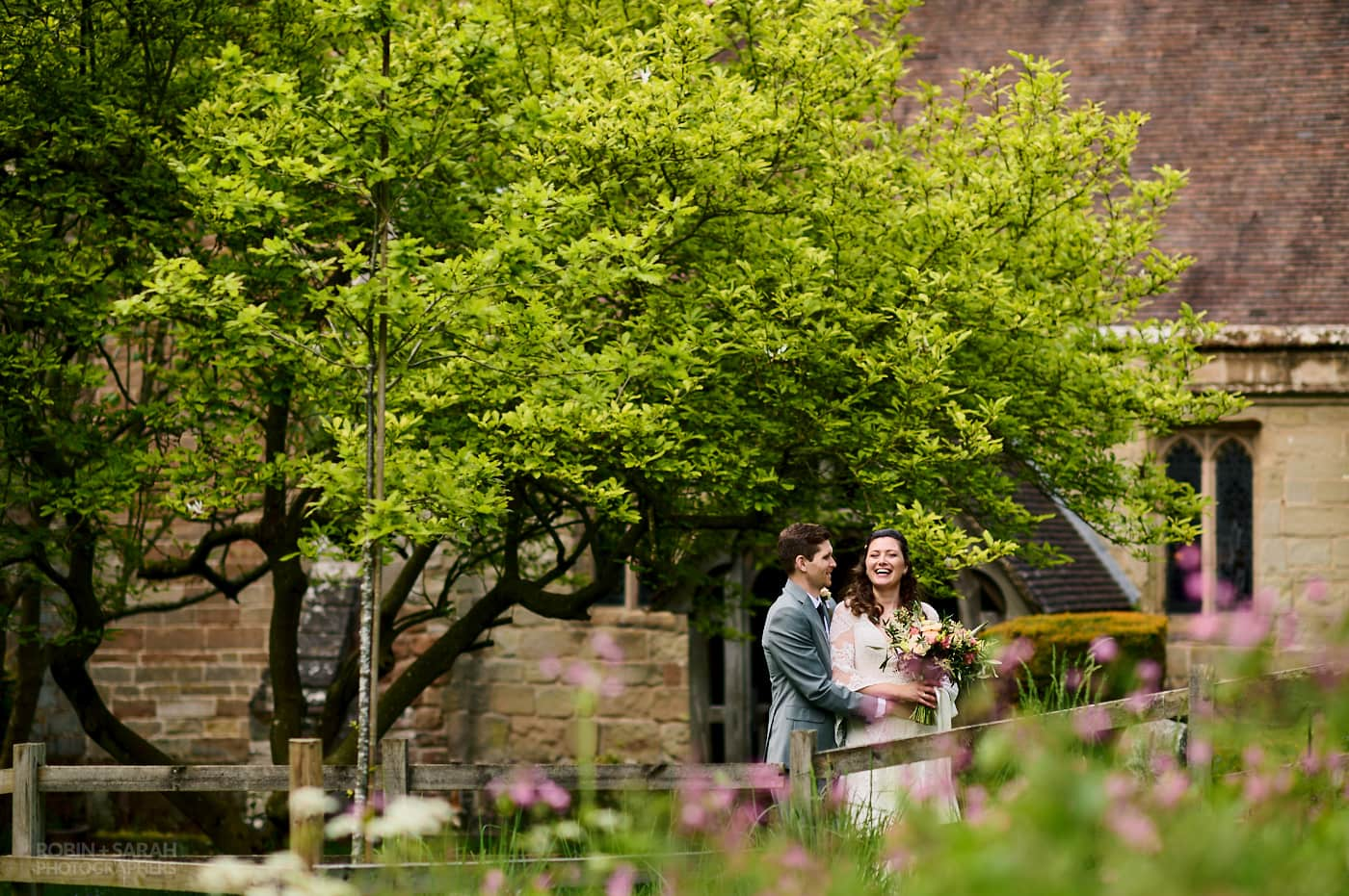 Bride and groom together in grounds at St Leonards church Beoley