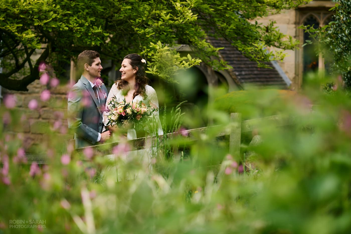 Bride and groom together in church grounds