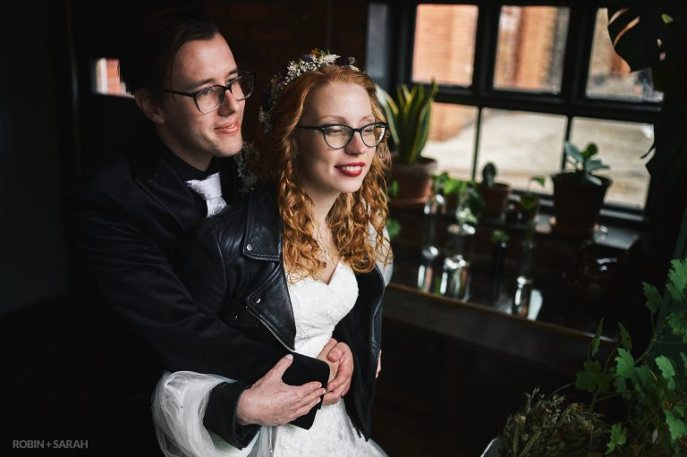 Alternative bride and groom in window light surrounded by potted plants