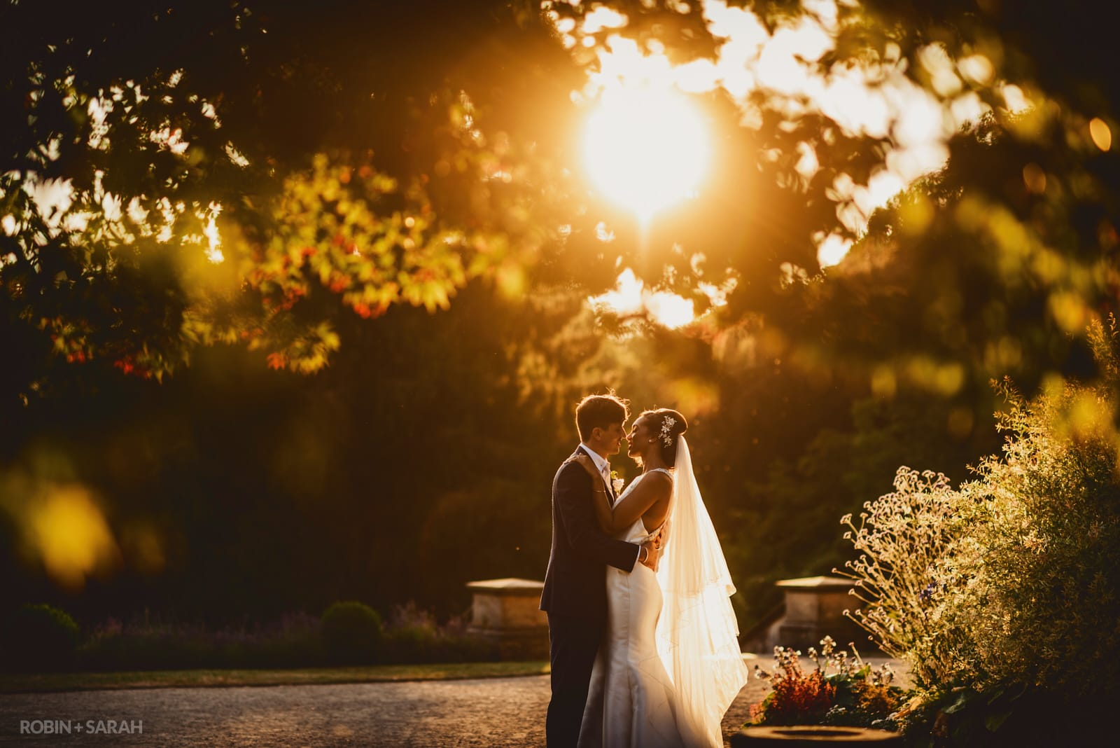 Bride and groom about to kiss under trees with beautiful sunset