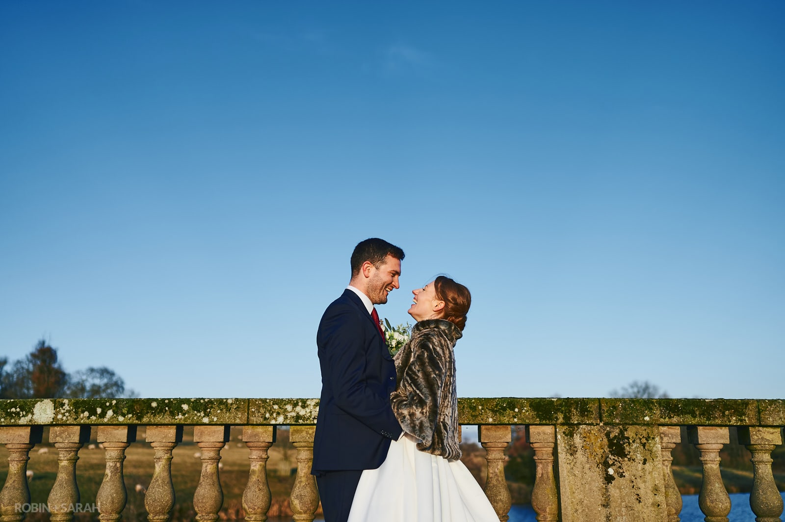 Bride and groom laughing together on cold winter day with clear blue sky
