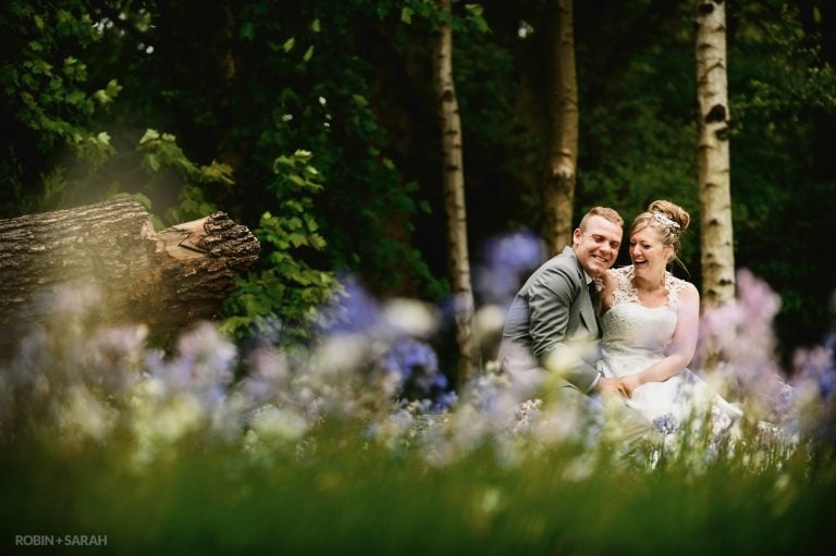 Bride and groom sitting in woodlands surrounded by bluebells laughing together