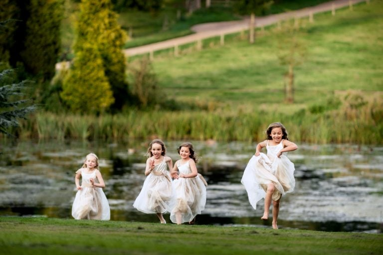 Flowergirls running across lawn with lake e in background